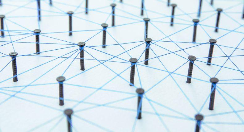 Dieses Bild zeigt Nägel, die durch blaue Fäden miteinander vernetzt sind. Dies soll die Vernetzung symbolisieren.